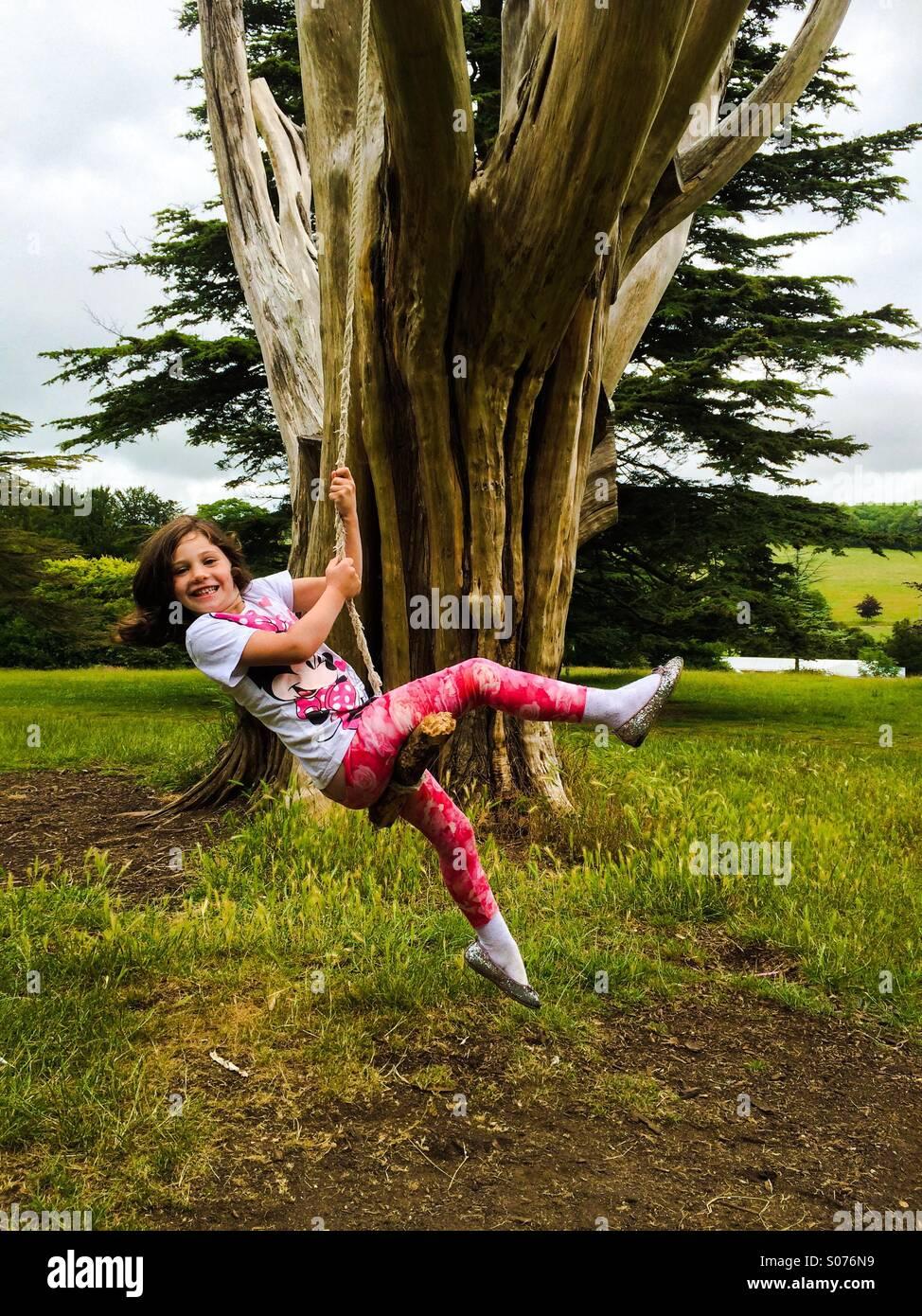 Petite fille de cinq ans sur tree swing Photo Stock