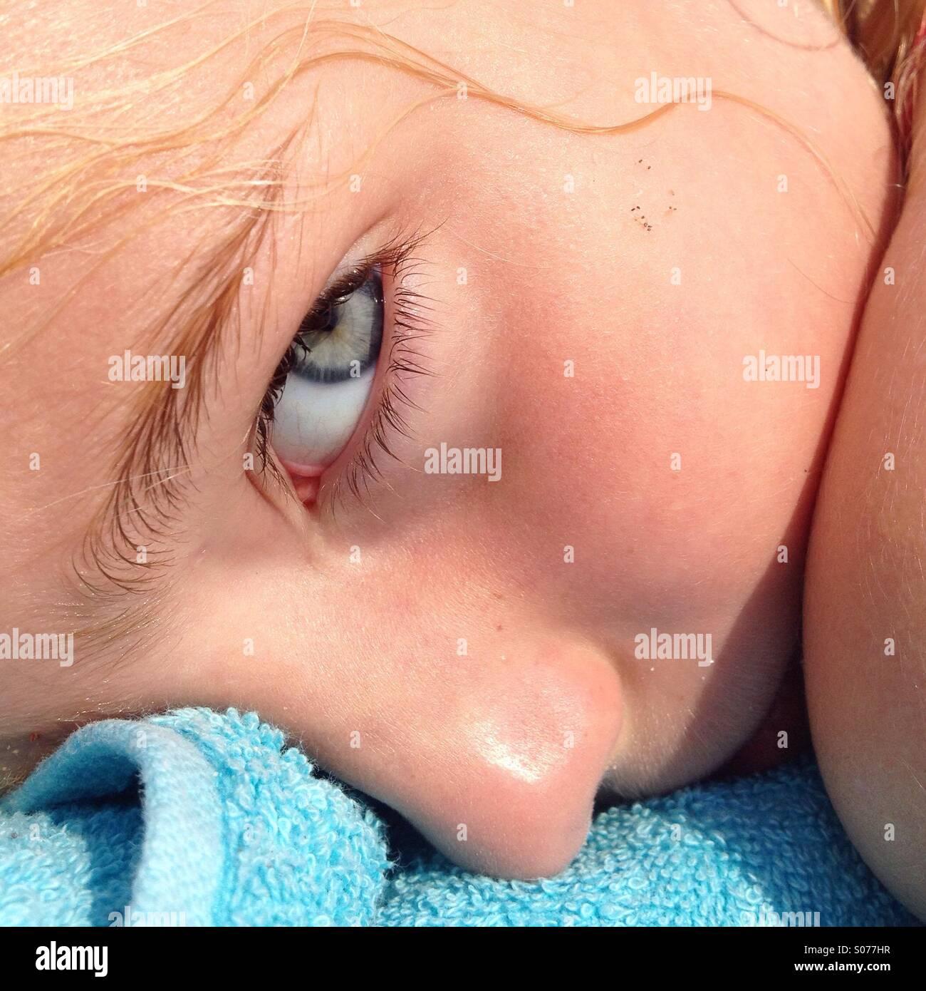 Un gros plan du visage d'une jeune fille se détendre sur une serviette de plage pendant des vacances en famille Banque D'Images