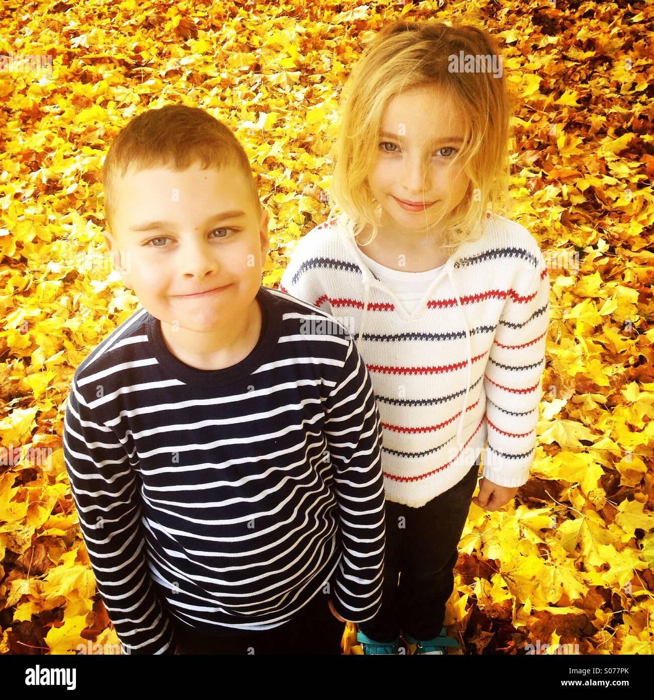 Un mignon petit frère et soeur dans un champ d'automne les feuilles d'automne jaune d'or Photo Stock