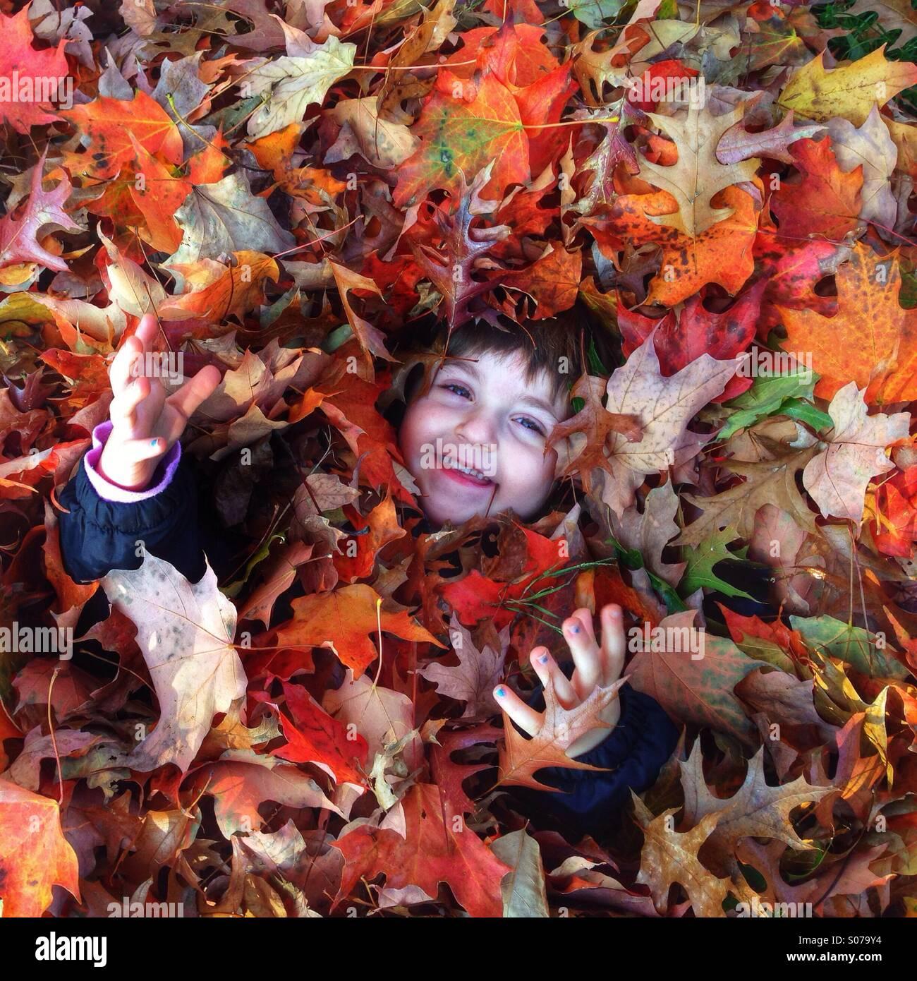 Jeune fille en tas de feuilles d'automne Photo Stock