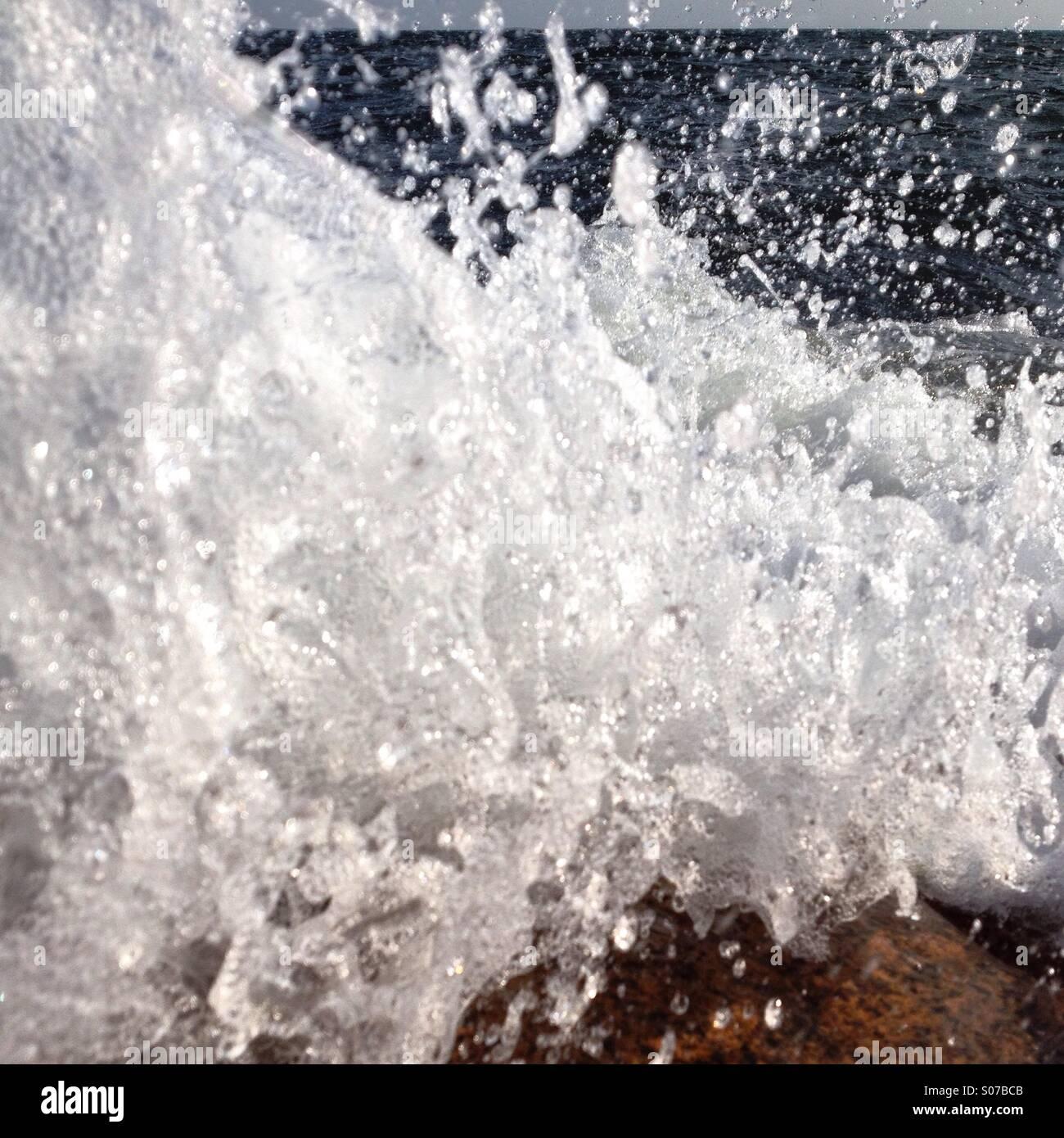 Une vague se brisant sur les rochers capturé au dernier moment avant qu'elle ne touche l'objectif Banque D'Images