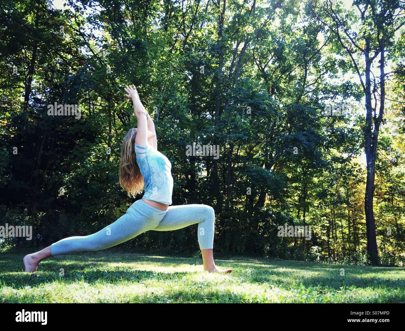 Une femme faisant du yoga à l'extérieur dans l'herbe entouré par la nature. Banque D'Images