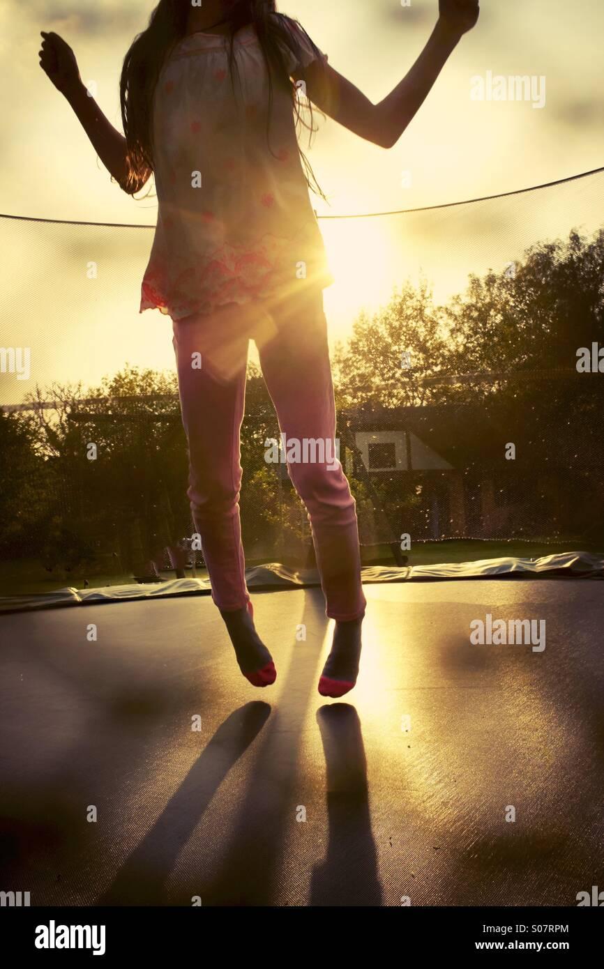 Le rebond. Une jeune fille de rebondir sur un trampoline de jardin Photo Stock