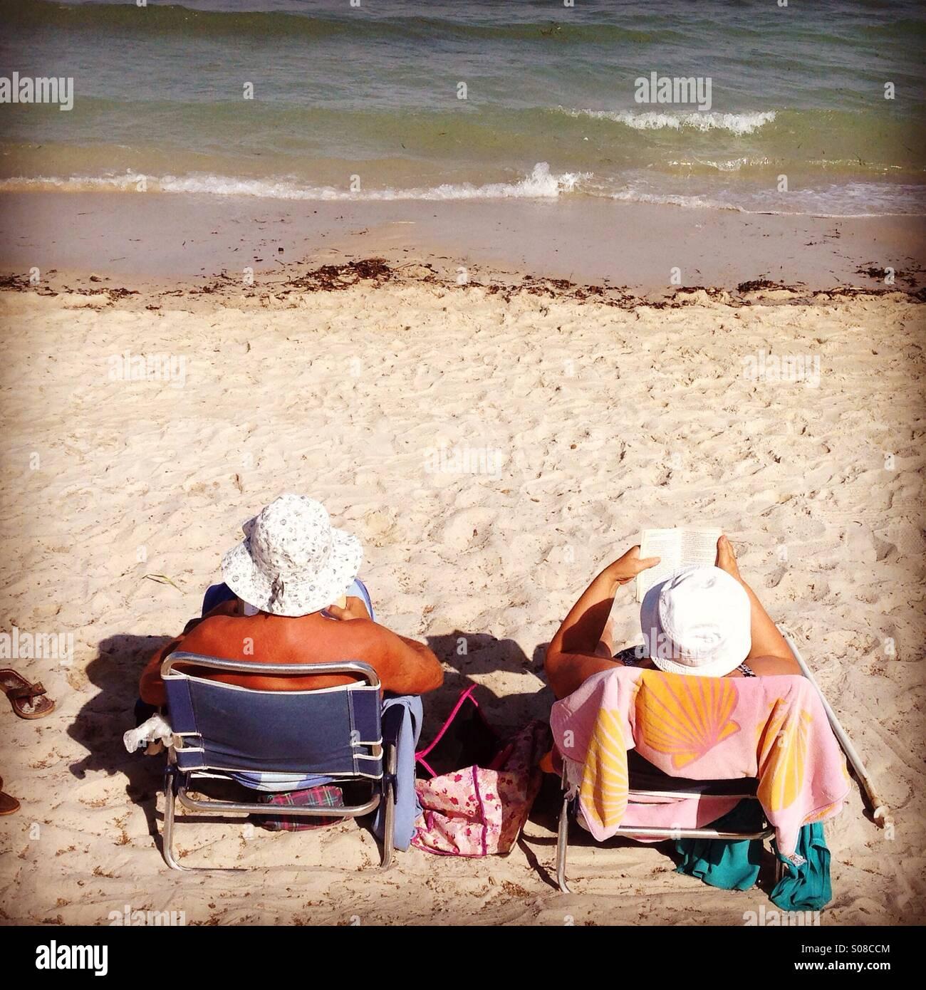 Deux retraités de la lecture d'un livre sur la plage Photo Stock