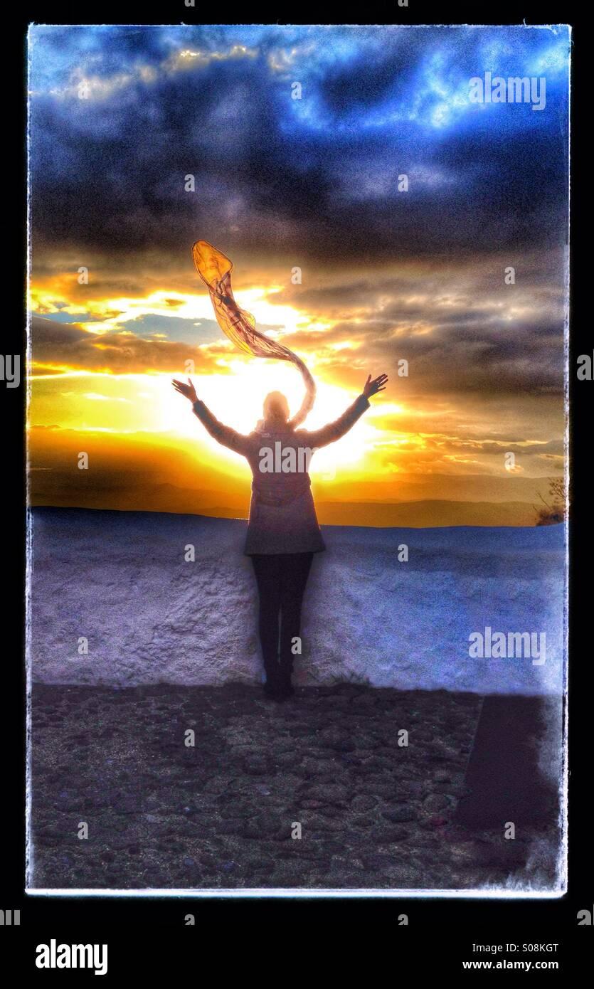 Femme avec foulard regardant le coucher du soleil Photo Stock