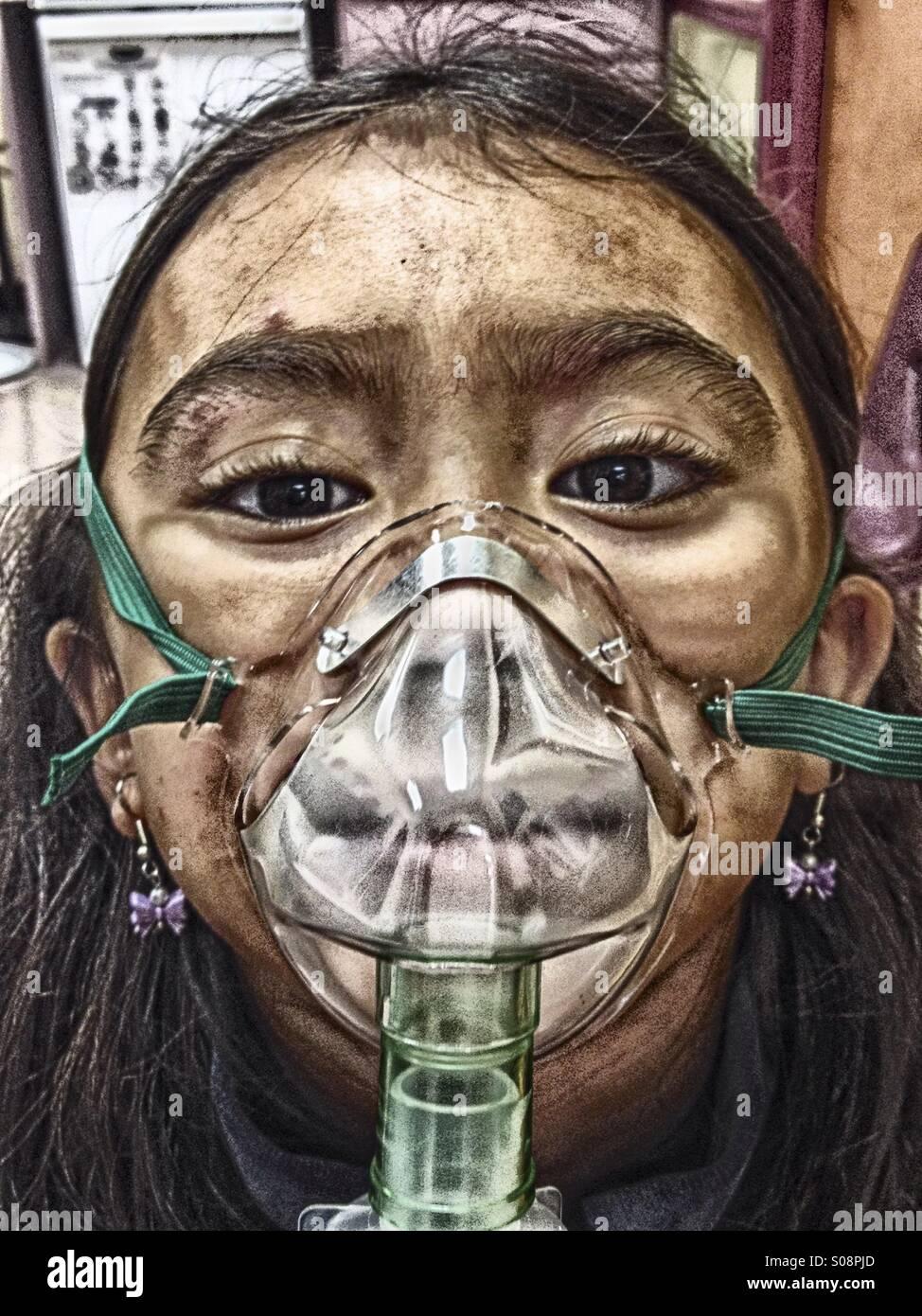 Petite fille recevant un traitement de la respiration avec un pulvérisateur après un accident. Photo Stock