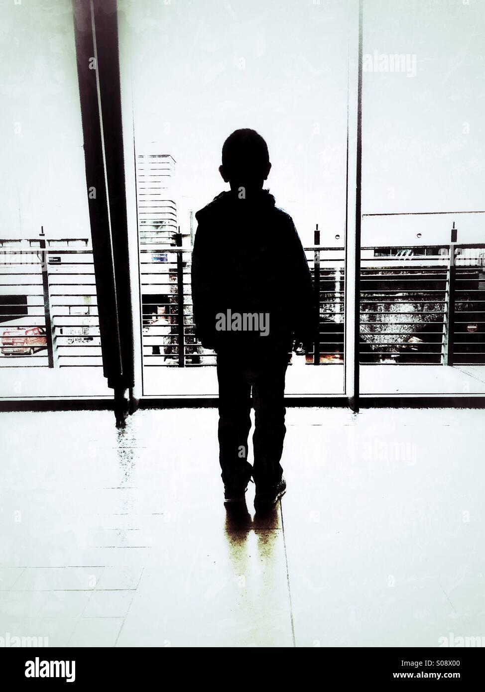 Garçon debout à l'intérieur d'un bâtiment Photo Stock