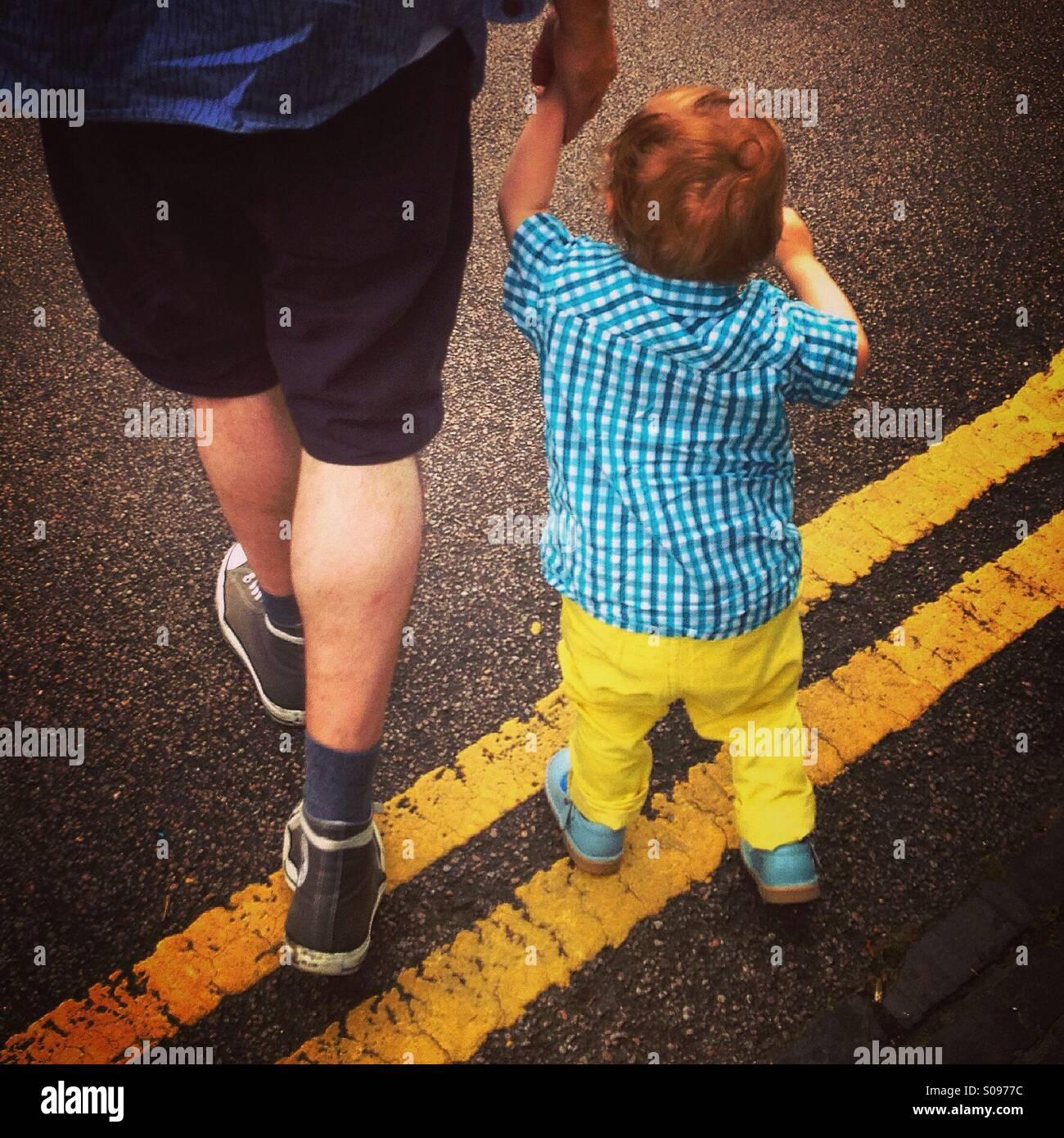 Père et fils marchant sur les lignes jaunes double sur une route de Londres. Photo Stock