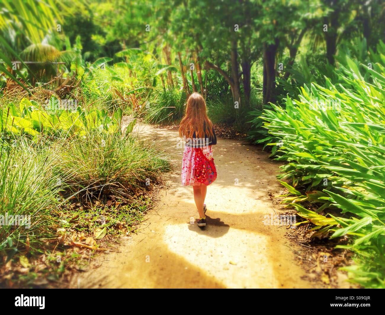 Une petite fille qui marche sur un chemin dans la jungle. Photo Stock