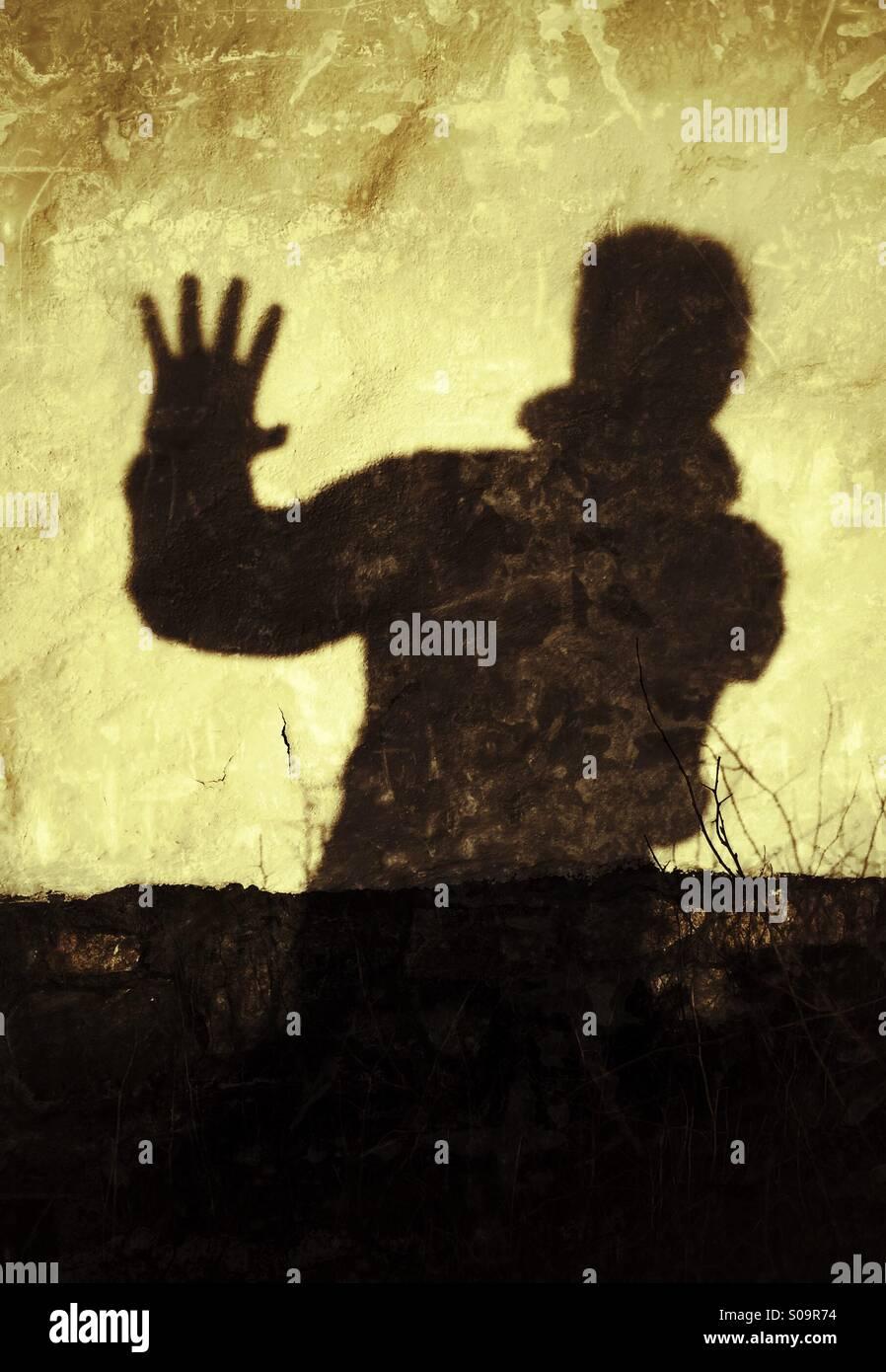 Stop! Pas plus! L'homme jette une ombre sur un mur d'exprimer, arrêtez!, pas plus! Photo Stock