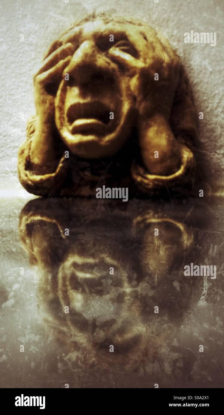 Tête sculptée en pierre appelé 'Misery' gargoyle (AKA grotesque) plaque murale à l'Université Photo Stock