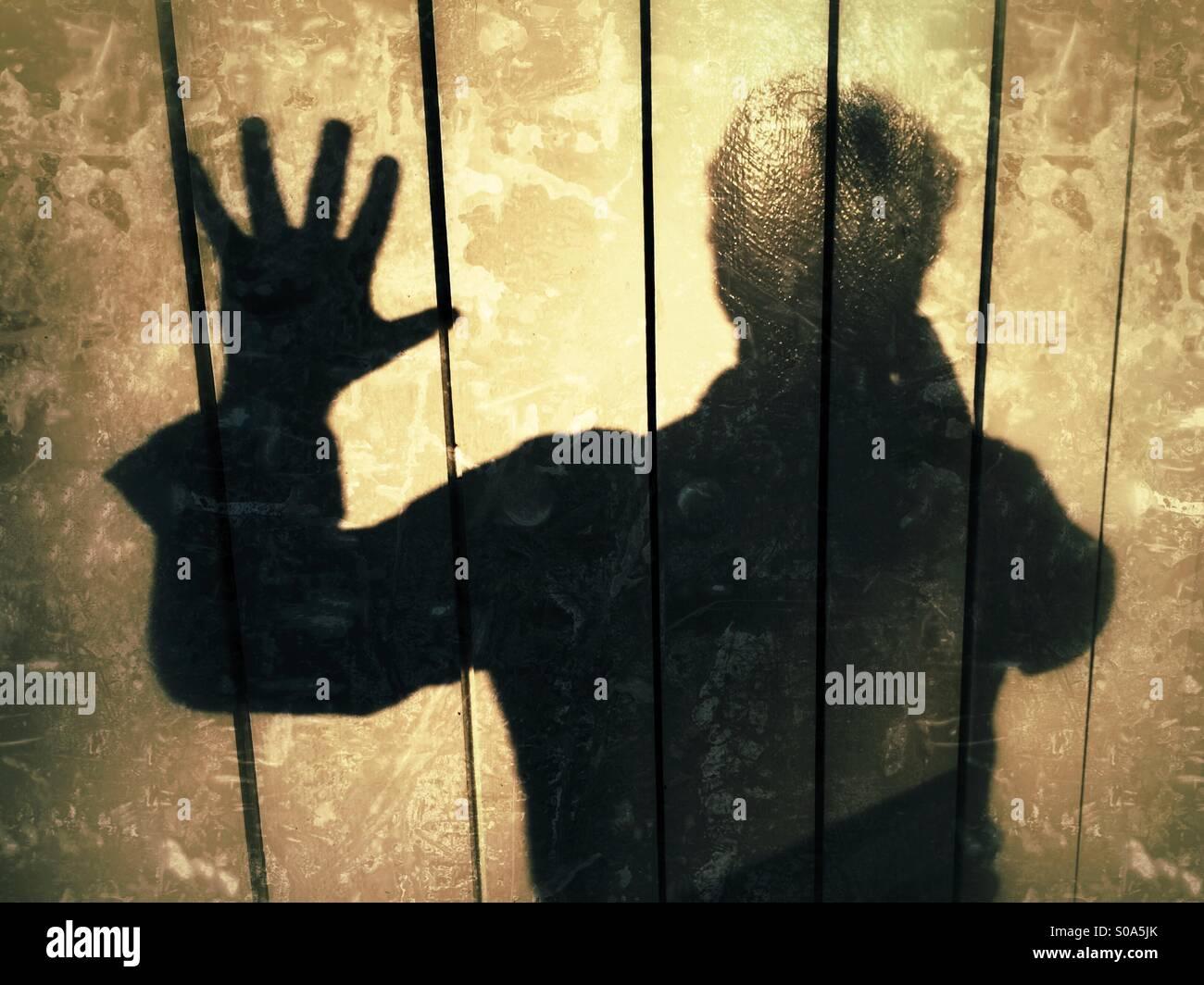L'homme jette une ombre sur un mur, exprimant, STOP!, pas plus! Photo Stock