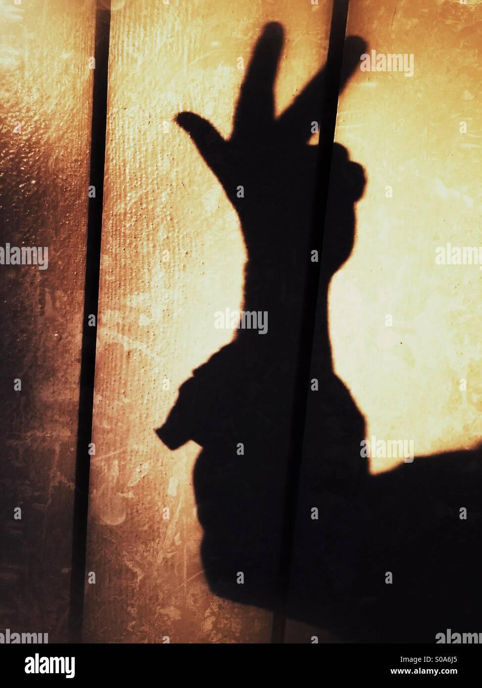 Un homme jette une ombre sur un mur, en comptant sur sa main. Numéro trois. Photo Stock