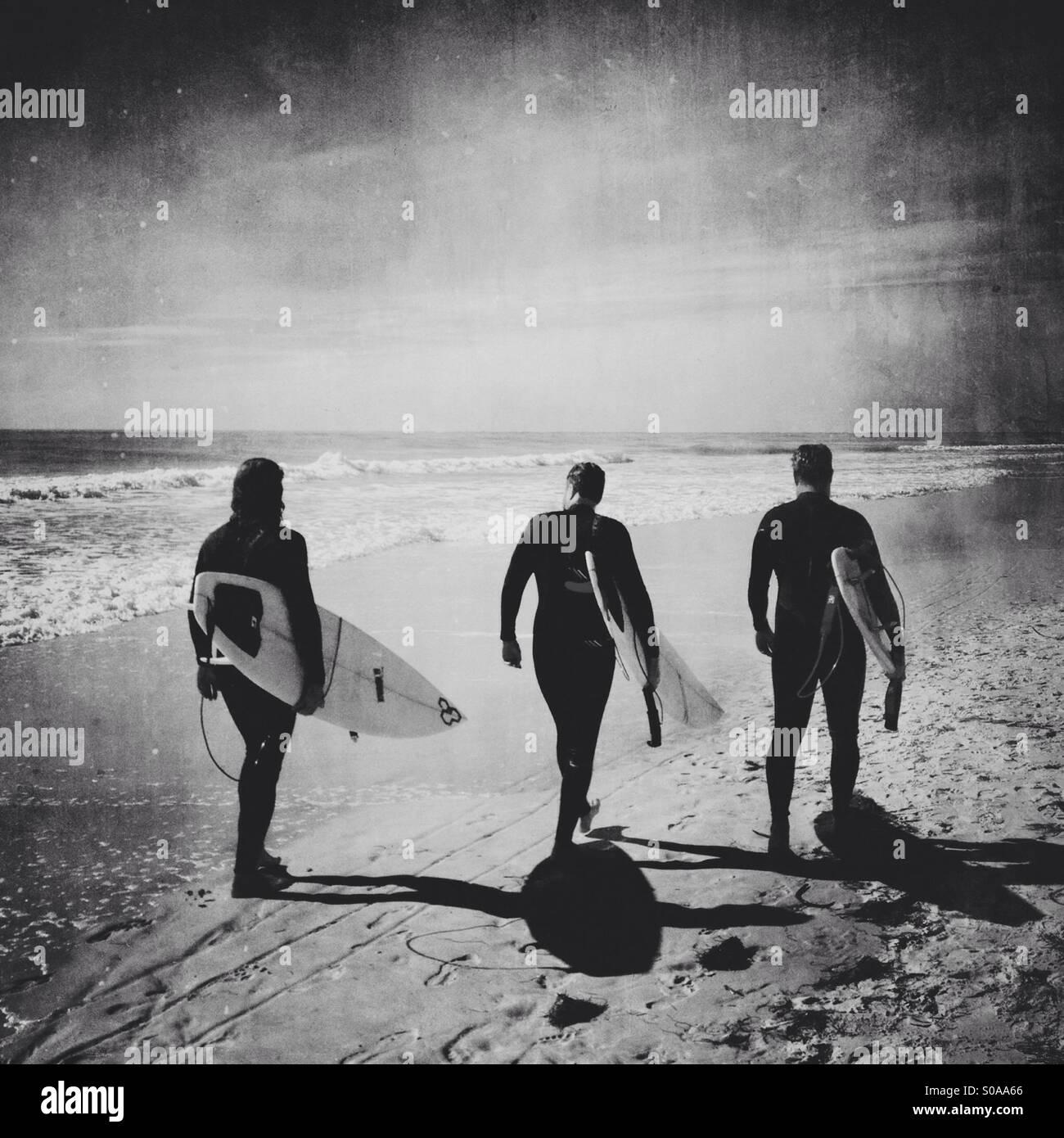 Trois surfeurs marchant sur la plage. Photo Stock