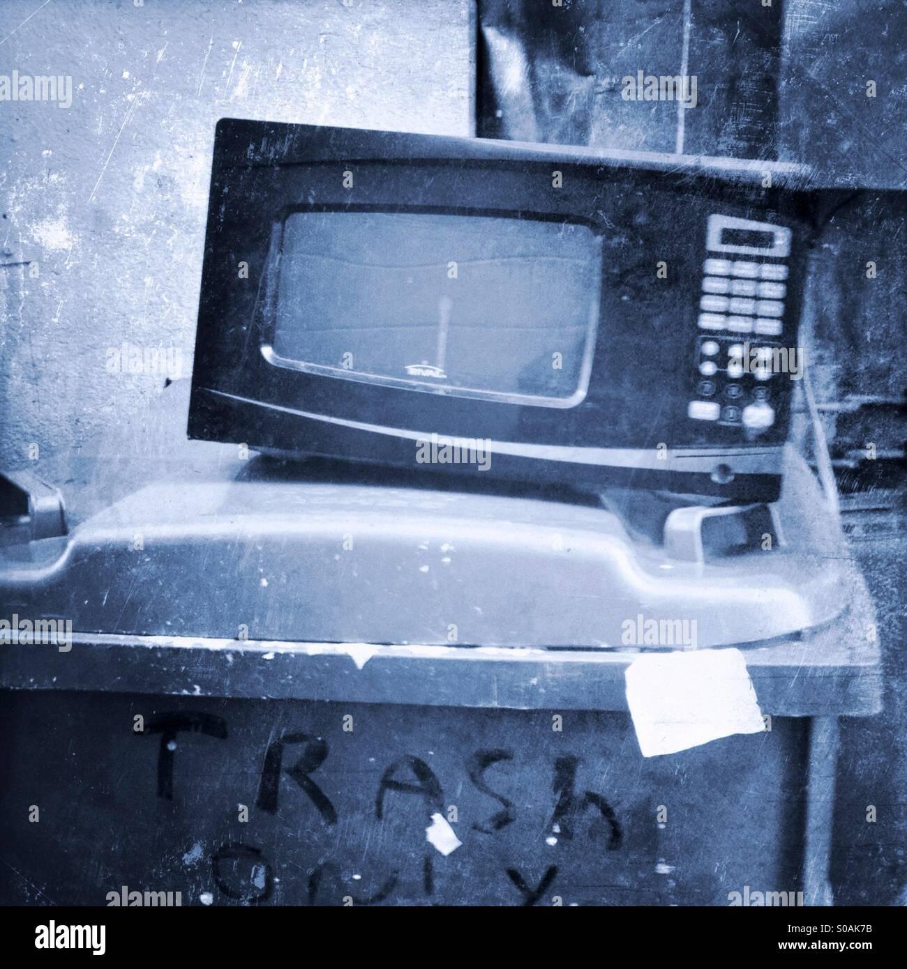 Four à micro-ondes assis sur une poubelle. Photo Stock