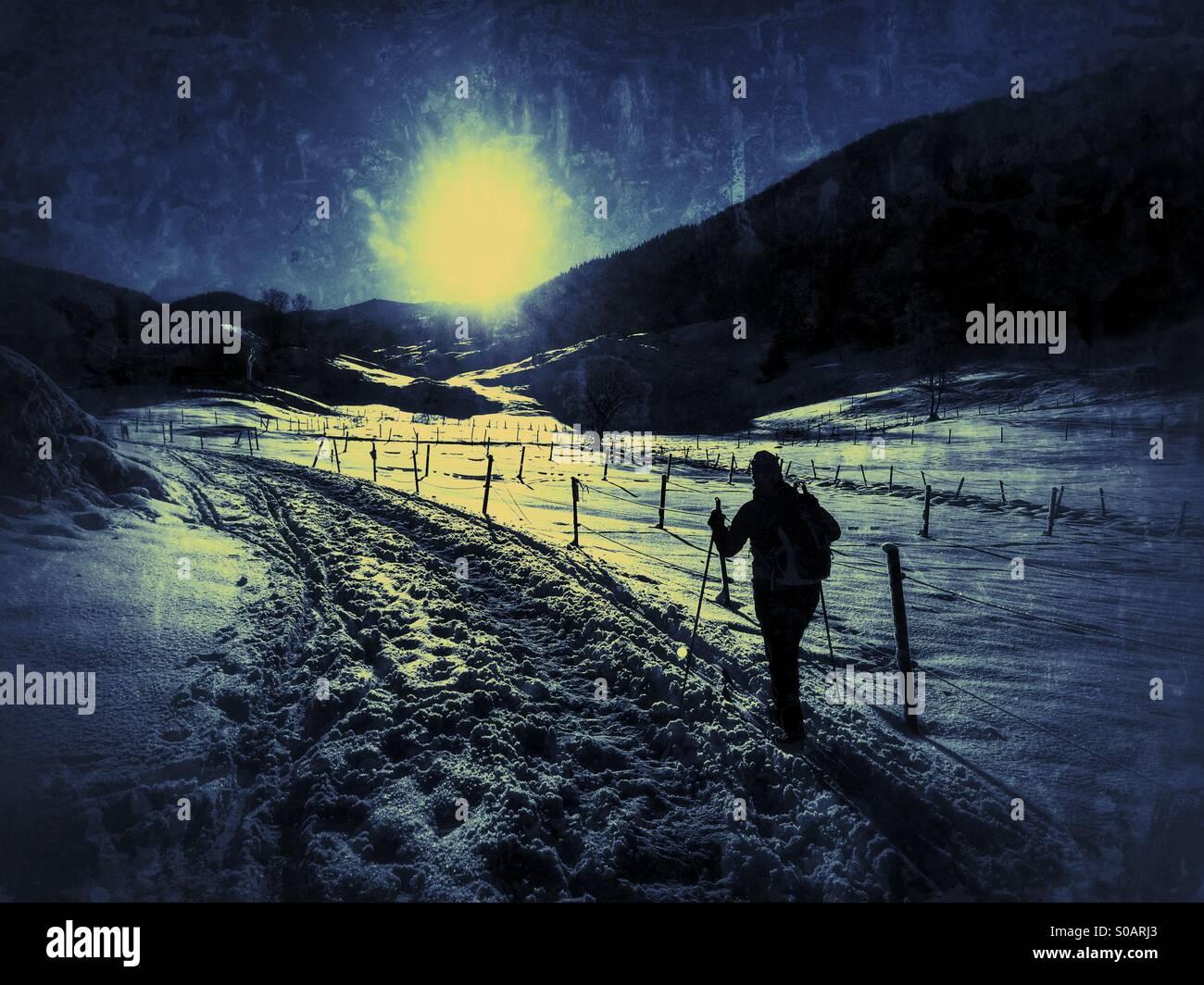 / Nordique de ski de fond, dans une vallée couverte de neige ski vers le soleil. Banque D'Images