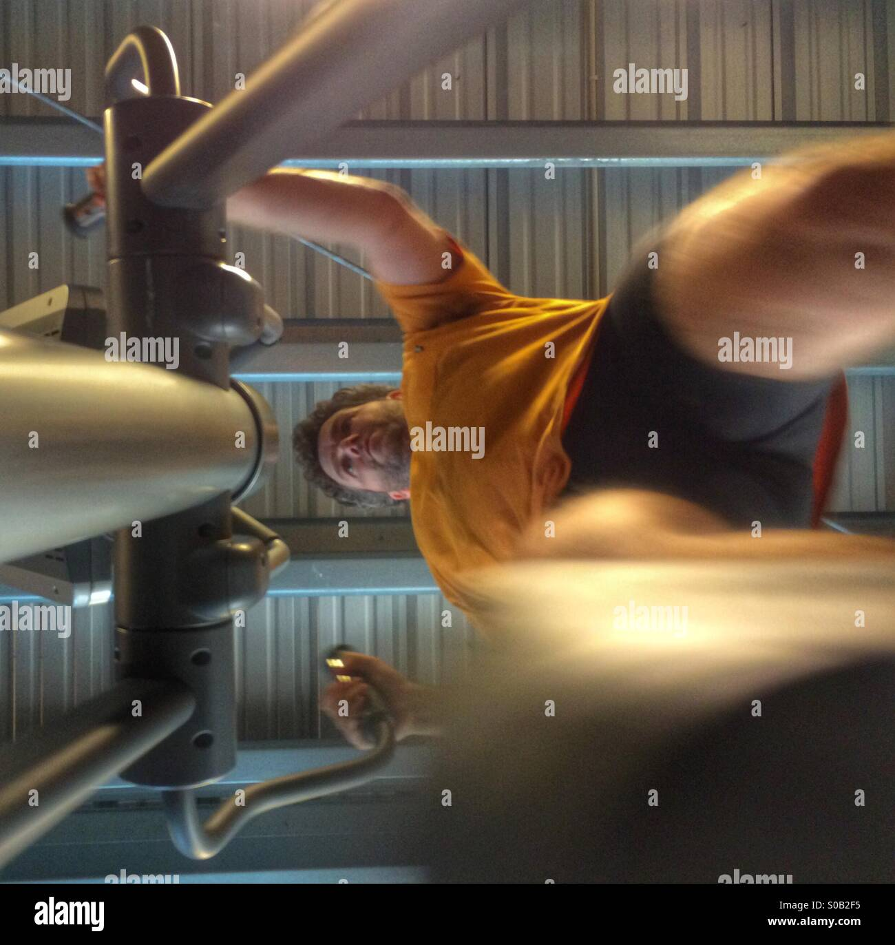 Âge moyen, caucasian man la formation sur une machine elliptique crosstrainer/formation dans un studio. Photo Stock
