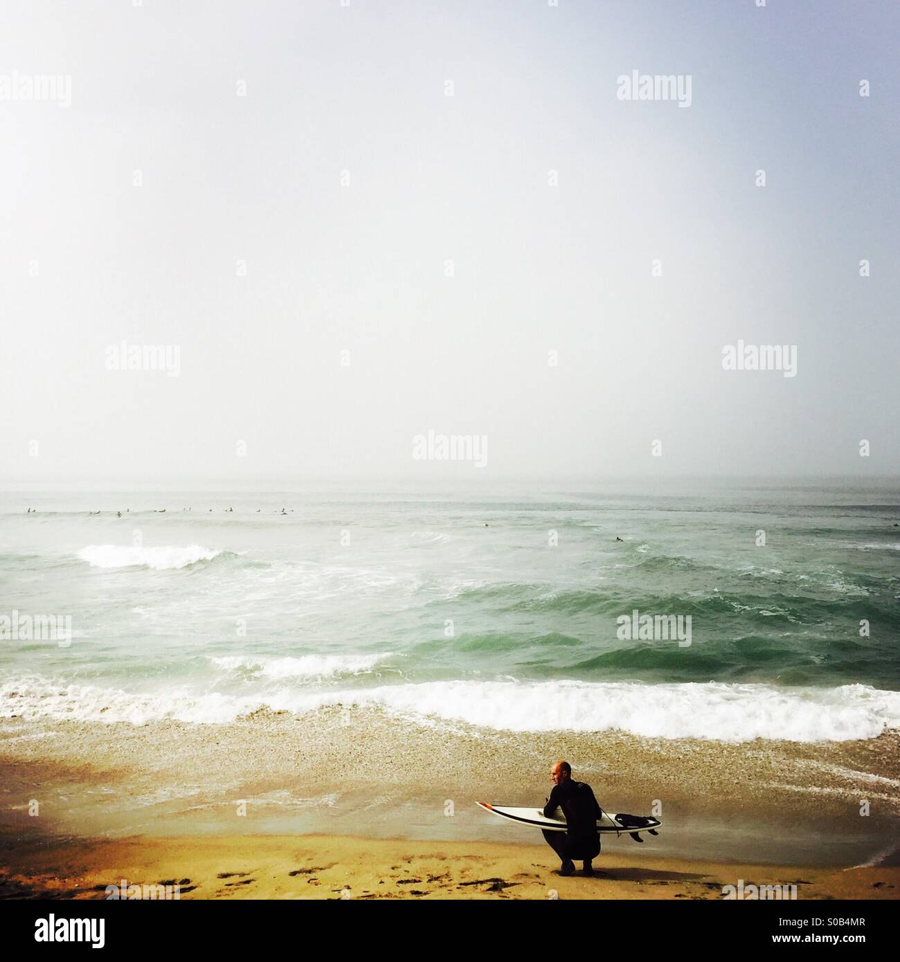 Un internaute attend sur la plage. Manhattan Beach, Californie, États-Unis. Banque D'Images