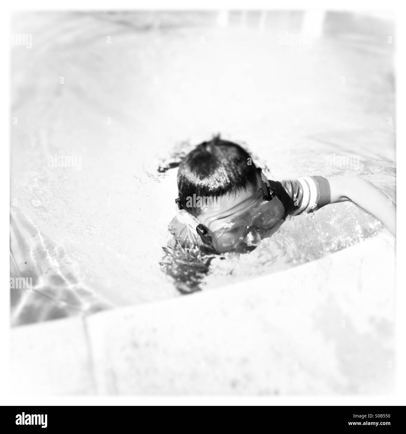 Un garçon de 7 ans nage jusqu'au bord d'une piscine. Photo Stock
