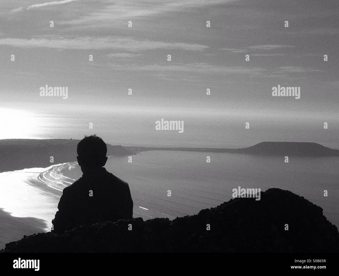 Adolescent chilling sur rocher à admirer la vue de la mer qui entoure la tête des vers, Gower. Silhouette Photo Stock