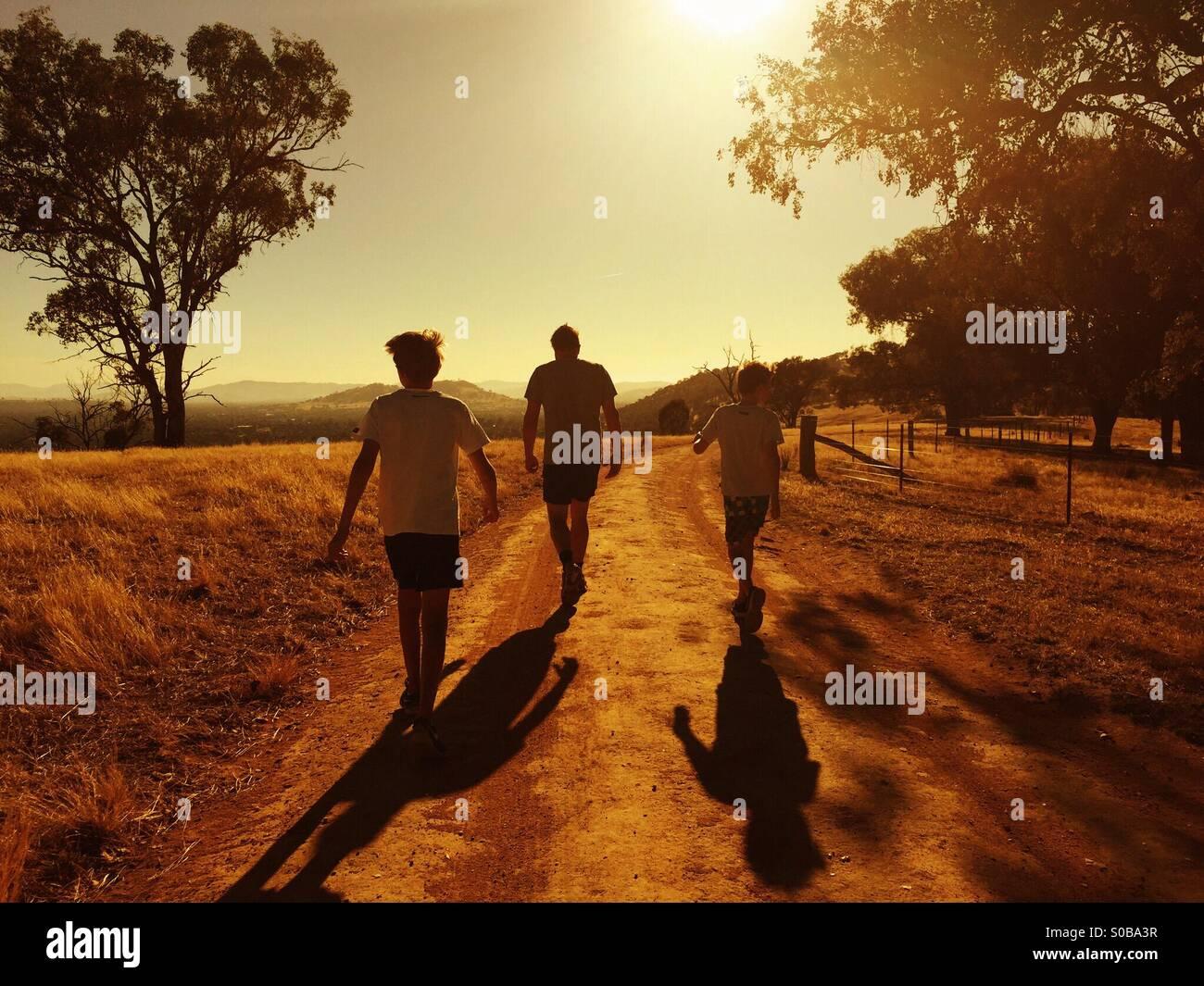 Un père et ses deux fils se réveiller dans le coucher du soleil en pays Australie Banque D'Images