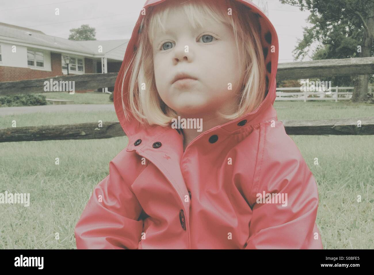 Jeune fille blonde portant un manteau de pluie rose assis sur le sol. Photo Stock
