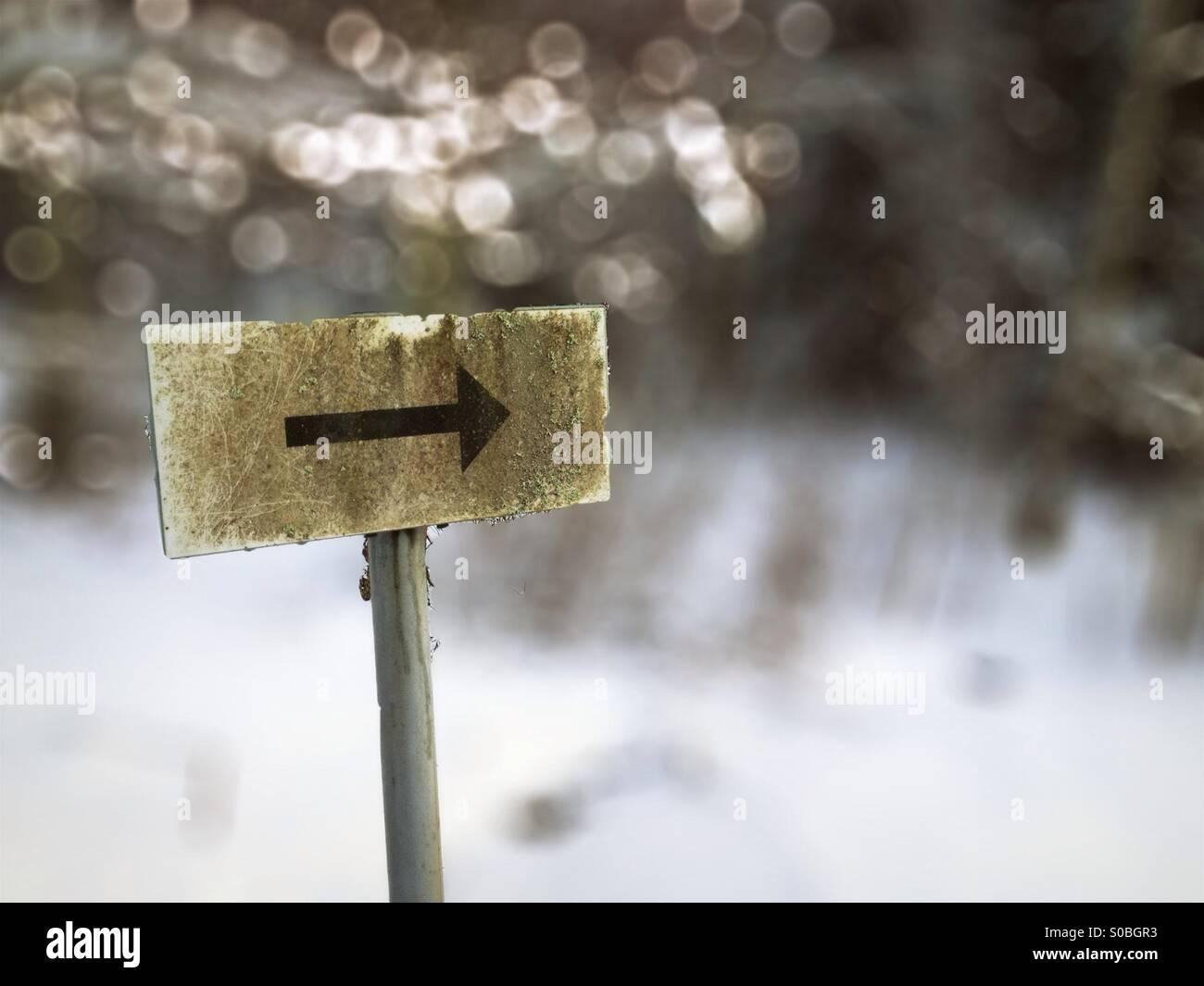 Panneau de flèche avec bokeh et neige en arrière-plan Photo Stock