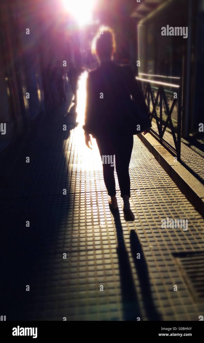 Vue arrière de woman walking along street vers le soleil Photo Stock