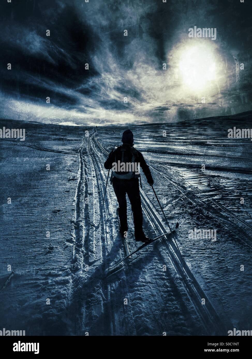 Skieur nordique chassant le soleil sous un ciel dramatique. Photo Stock
