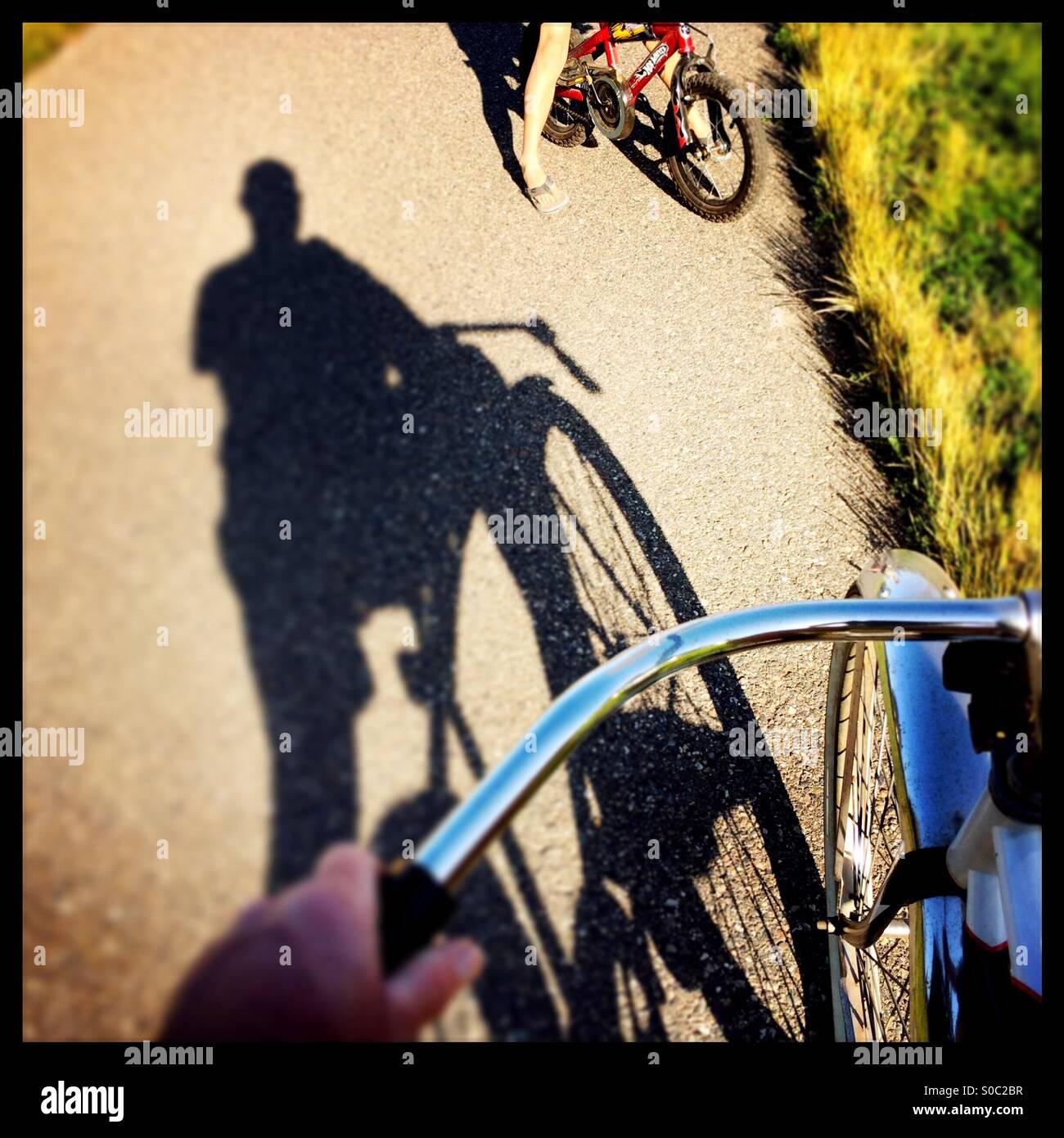 L'ombre d'un cycliste sur une piste cyclable de parler à un enfant de faire du vélo. Photo Stock