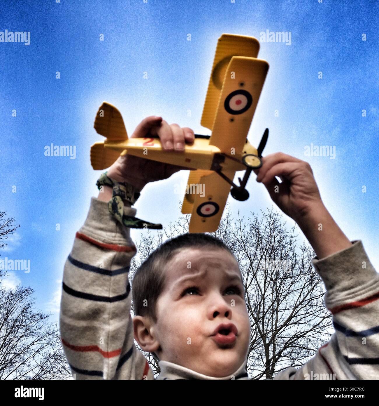 Jeune garçon jouet volant un biplan Photo Stock