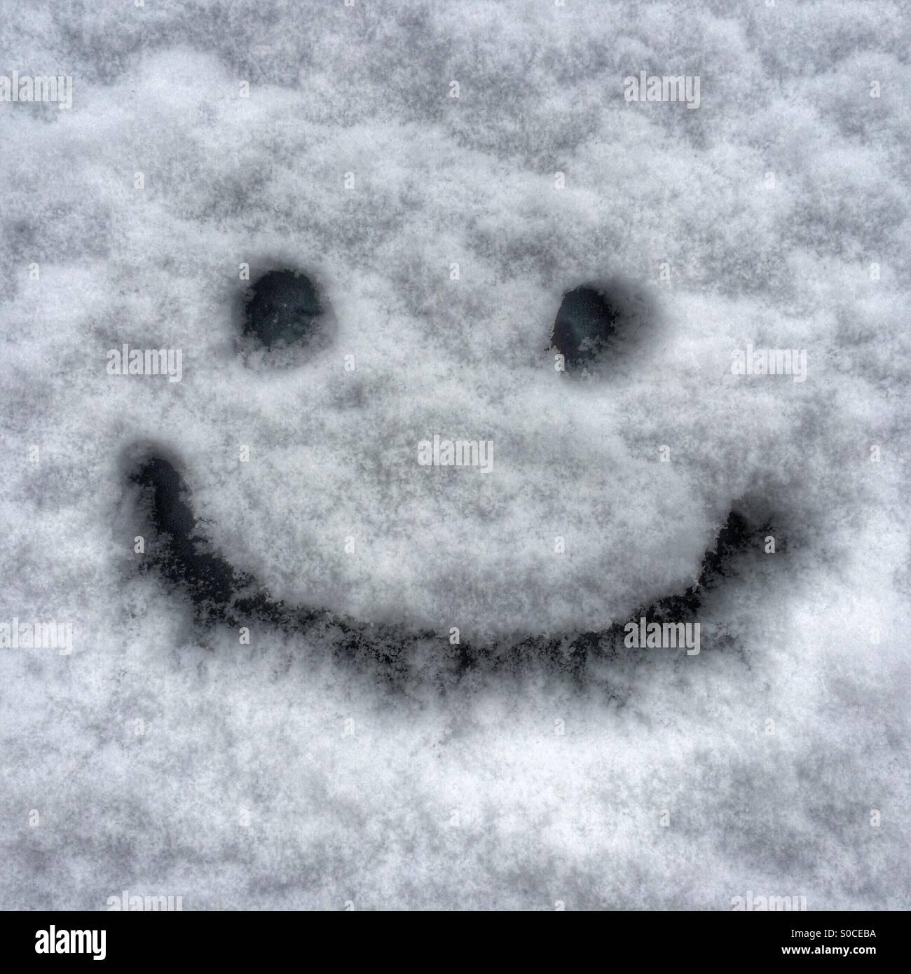 Ne vous inquiétez pas, être heureux - un smiley dessiné sur un pare-brise de voiture enneigée Photo Stock