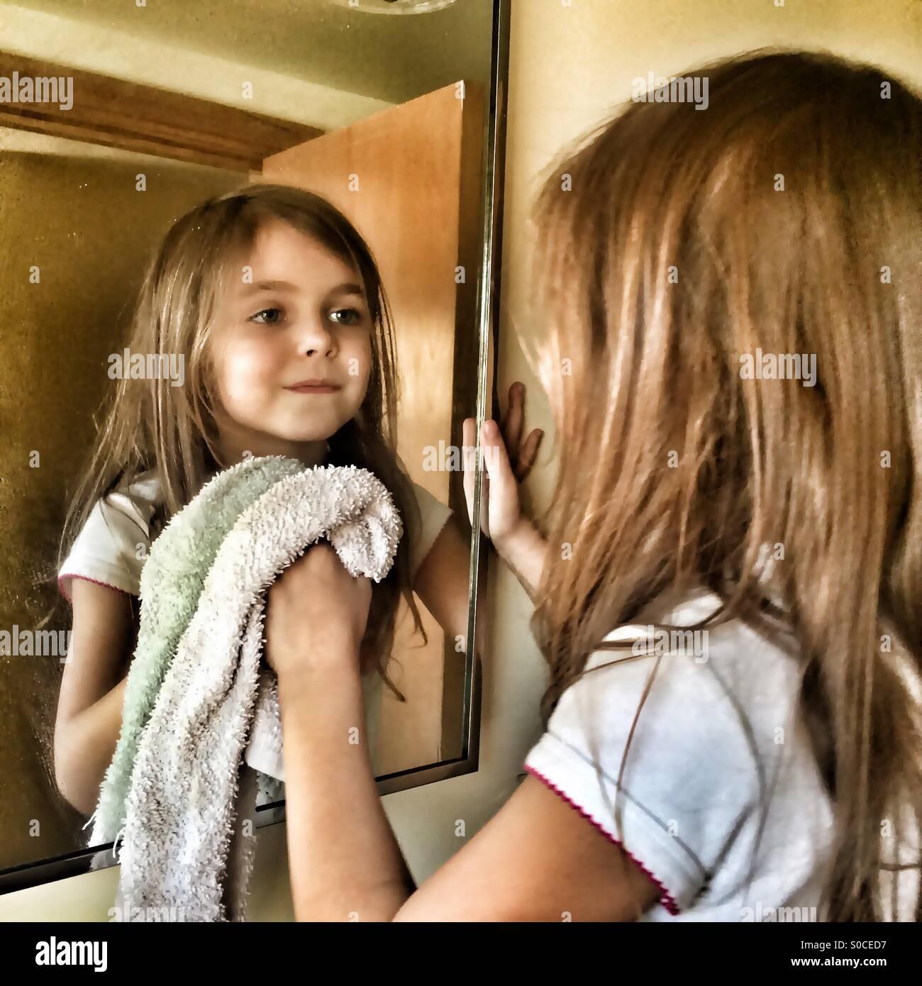 Jeune fille lave un miroir et regarder son propre reflet Photo Stock