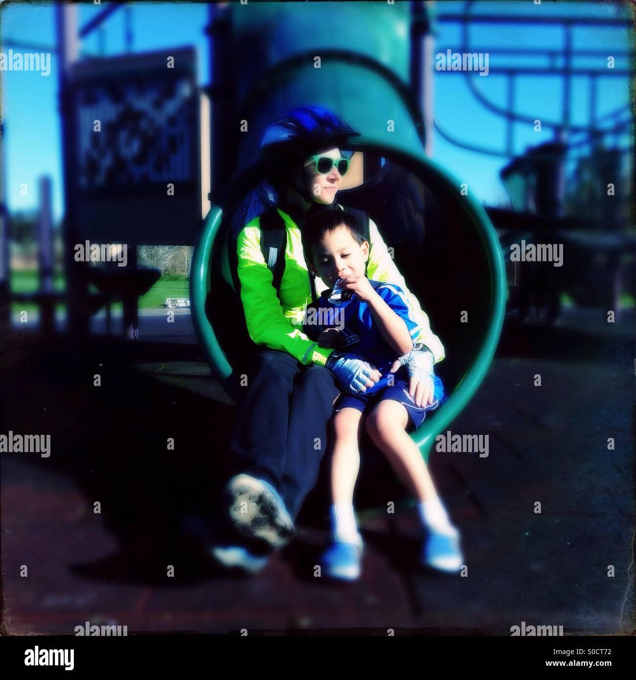 La mère et l'enfant sur l'aire de glisse Photo Stock