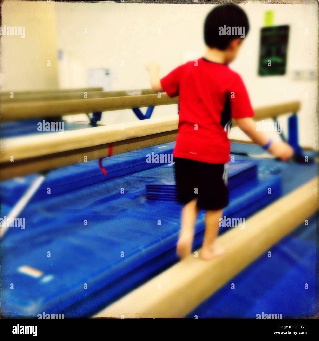 Garçon sur la gymnastique poutre Photo Stock