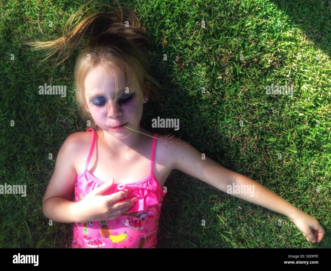 Petite fille se reposant sur la pelouse. Photo Stock