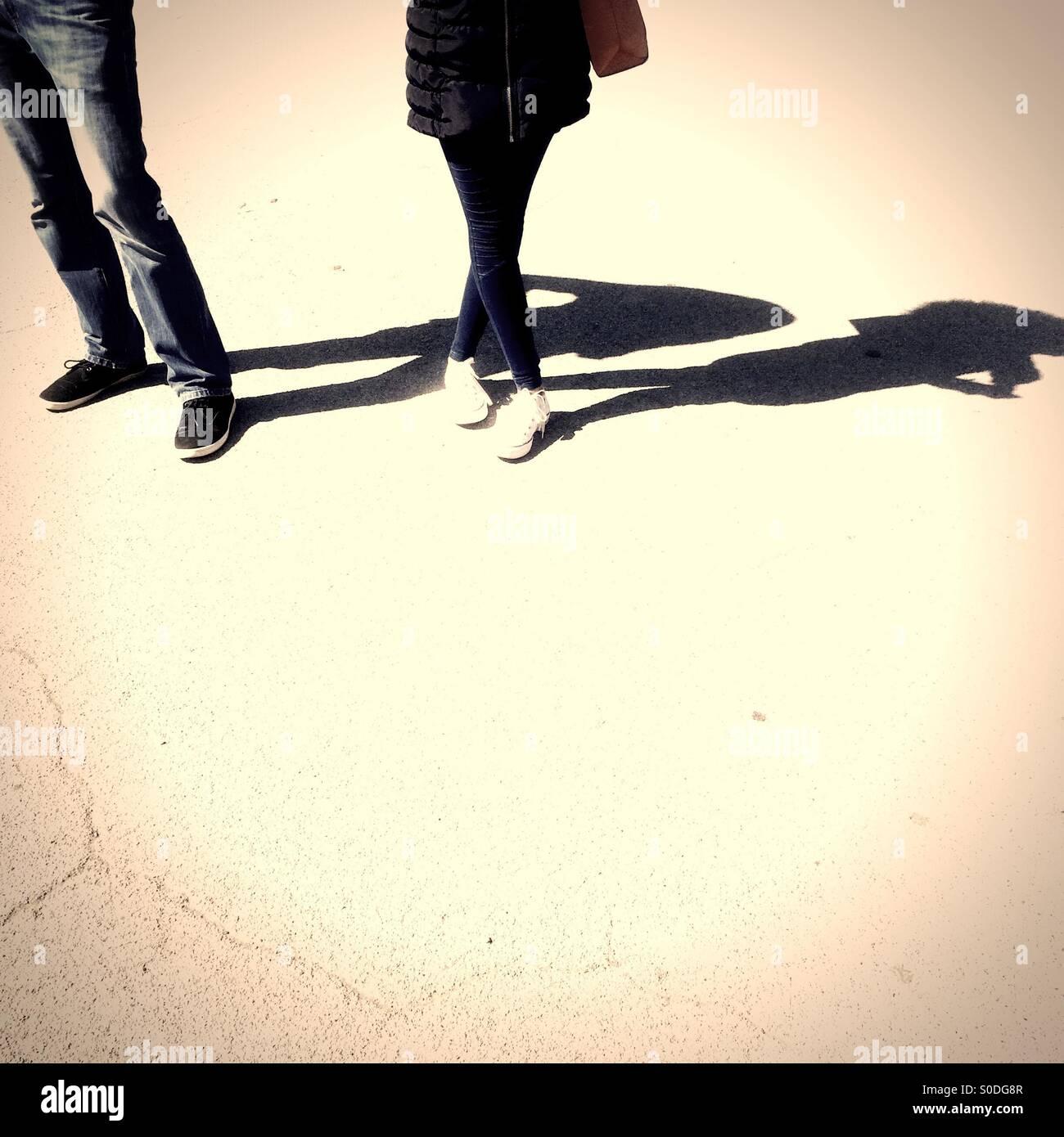 Couple debout sur le béton sur journée ensoleillée à l'ombre qui plane Banque D'Images
