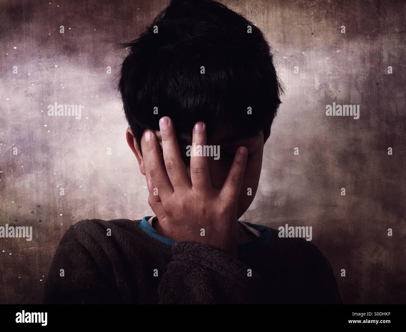 Garçon misérable de se cacher le visage avec la main Photo Stock