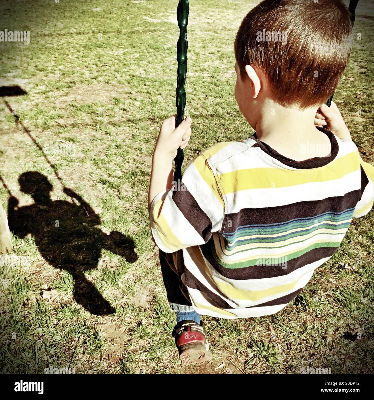 Jeune garçon balançoires et admire son image de l'ombre Photo Stock