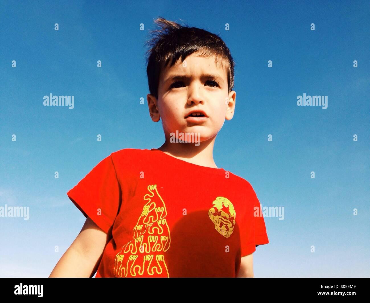 Un garçon de trois ans dans un t-shirt rouge Photo Stock