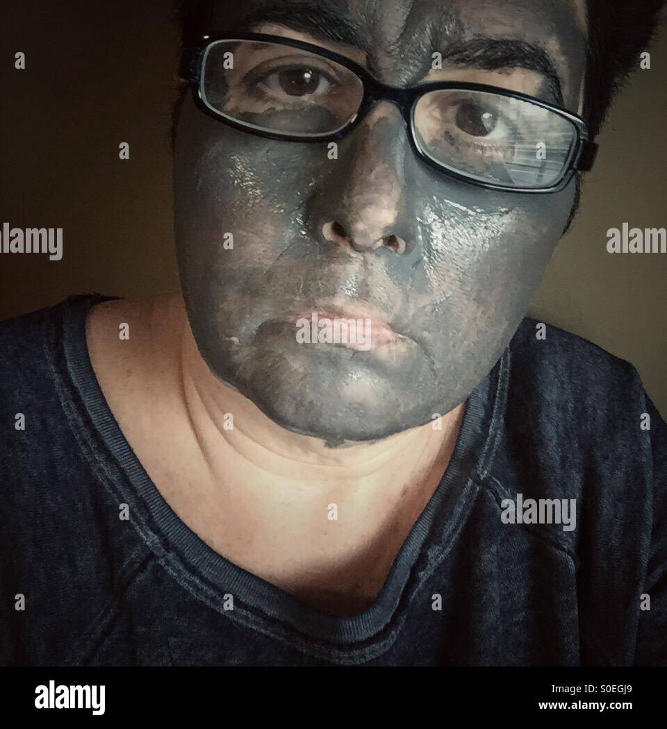 Une femme portant des lunettes avec un masque de boue sur son visage Photo Stock