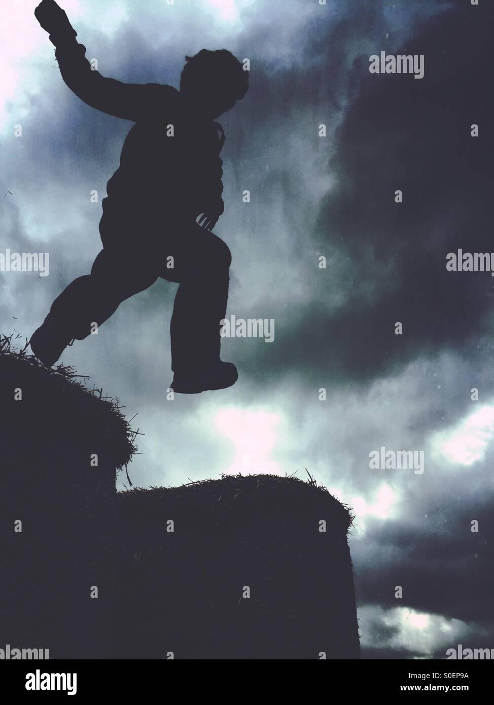 Silhouette d'un garçon sautant Banque D'Images