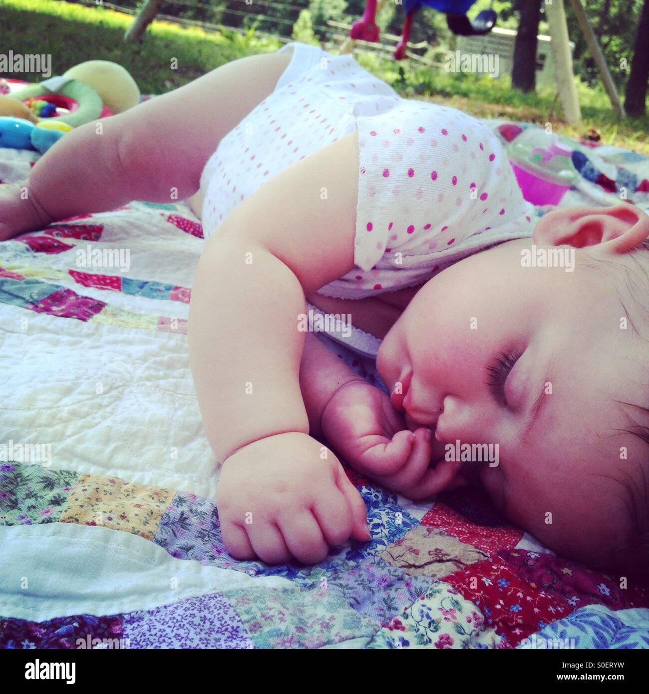 Bébé à dormir en dehors de la sieste sur un quilt Photo Stock