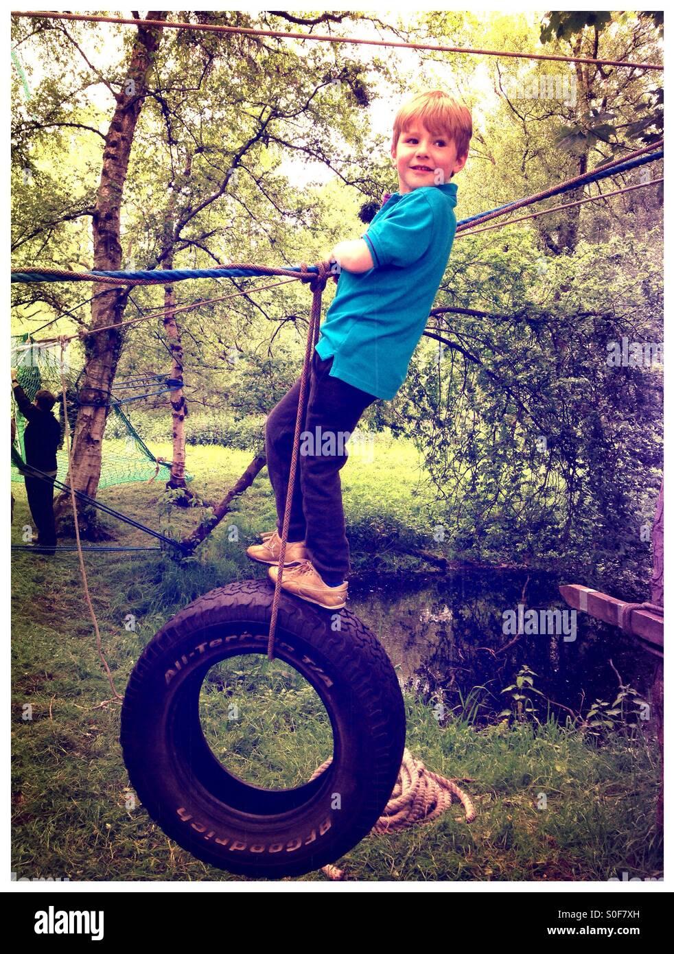 Boy swinging sur une corde et tire. Cours d'aventure. Parcours du combattant. Jeux forestiers Photo Stock