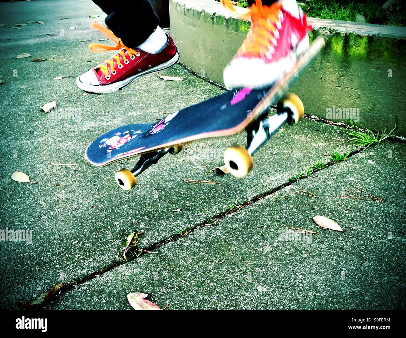 Obtenir de l'air, coups de pied, saut, en skateboard tandis que clad dans red sneakers avec lacets orange. Photo Stock