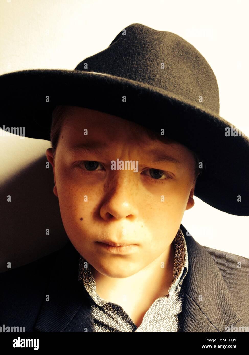 Un garçon de 10 ans portant un chapeau Photo Stock