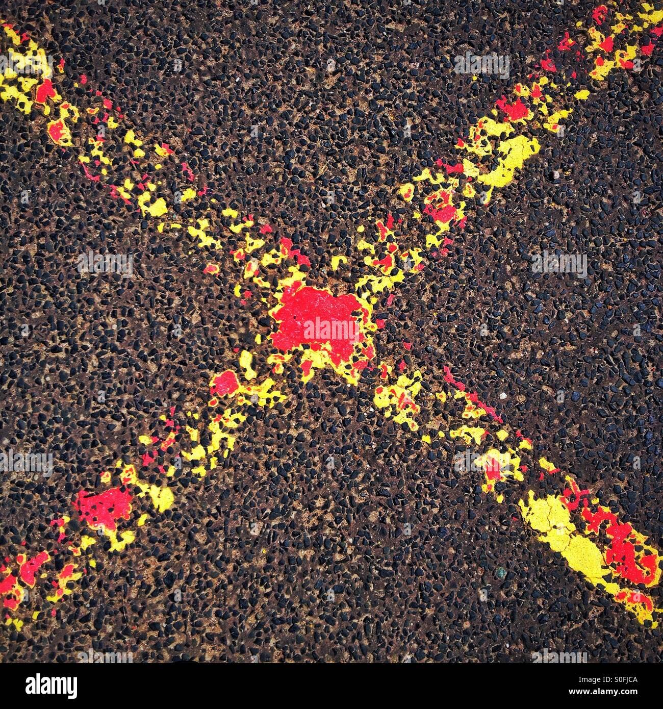 Le marquage routier. Croix rouge et jaune. Photo Stock