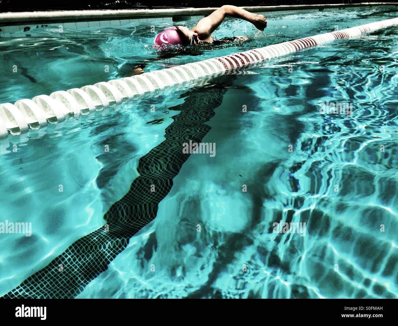 Voir à partir de la voie adjacente, une jeune femme australienne (freestyle) ramper dans la piscine olympique Photo Stock