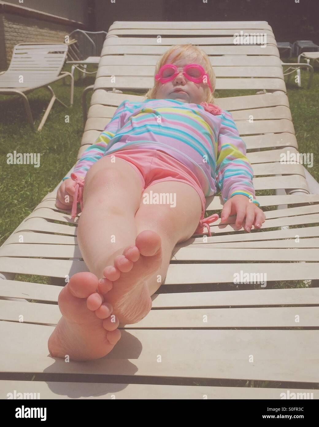 Jeune fille se détendre sur une chaise longue le port d'un maillot de bain et lunettes de natation. Photo Stock