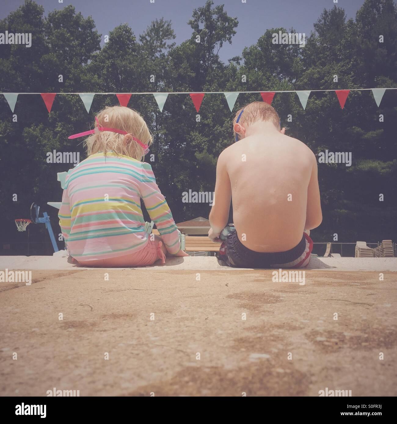 Deux jeunes enfants assis à côté de l'autre sur le côté d'une piscine. Photo Stock